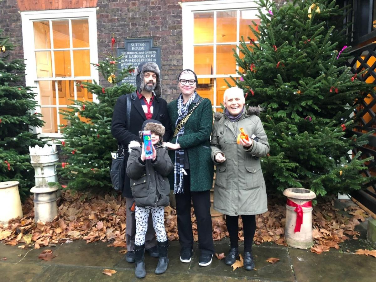 Catherine and her family stand in front of Christmas trees.
