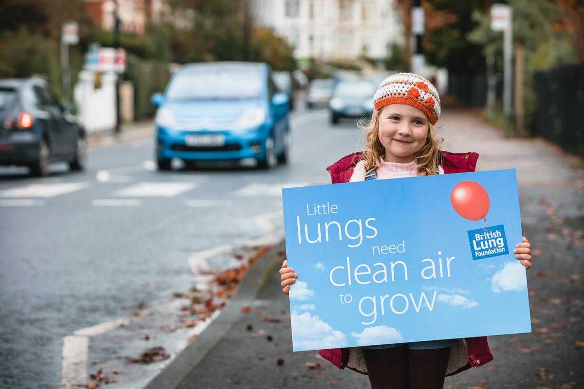 Girl smiling with British Lung Foundation placard next to a road with air pollution