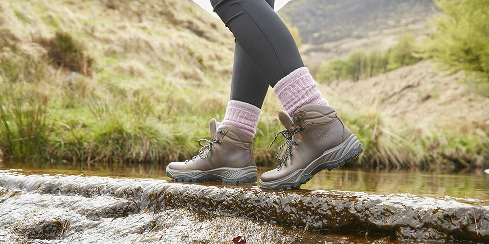 A woman wearing Millets boots walks along a wet path.