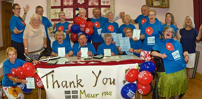 16 members of a singing for lung health group wearing British Lung Foundation t-shirts pose for a thank-you picture.