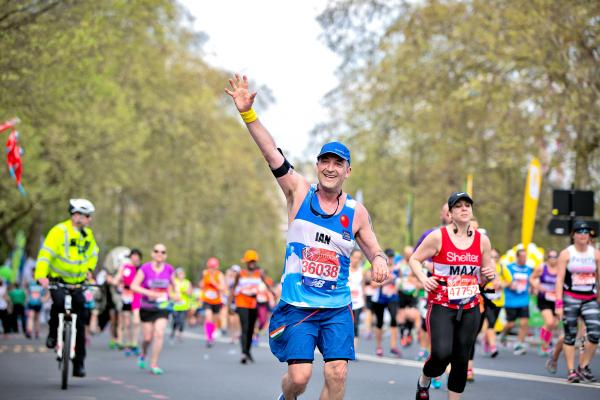 Marathon runner with hand up