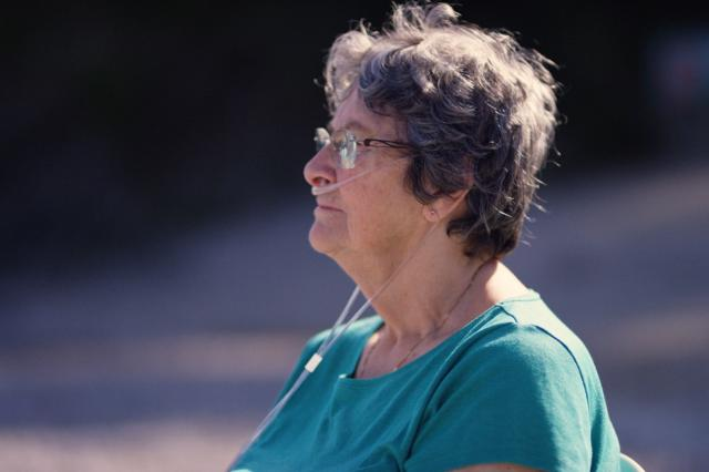 Ann sat on a small beach by the sea. She is wearing a nasal cannula to help her breath.