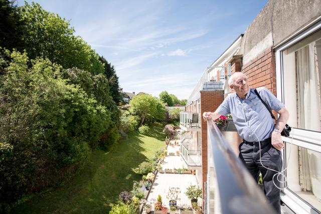 Eastbourne Man in sun hot weather on balcony