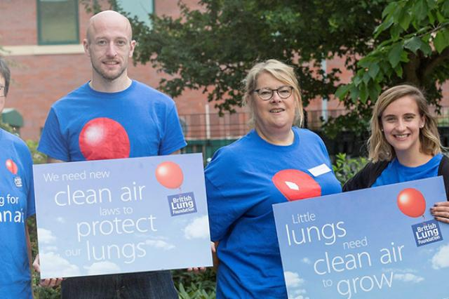 """A group of five people, wearing British Lung Foundation t-shirts, holding signs that read """"we need new clean air to protect lungs""""."""