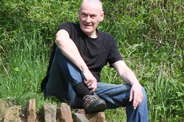 Eamon after taking part in the Active Steps programme. He is in the countryside, sat on some rocks.