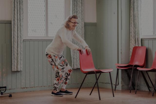 Woman exercising with a chair, the image has a dark tint