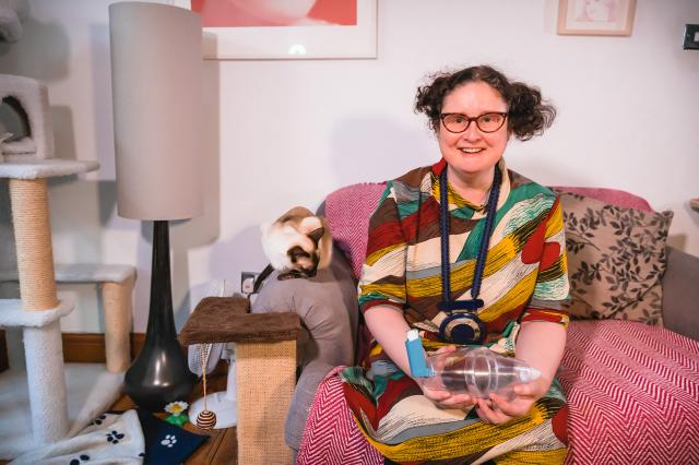 Woman sitting on sofa with inhaler and cat