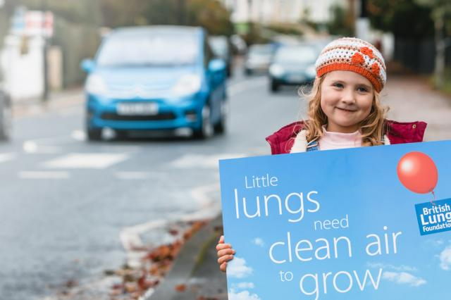 banner image of girl holding placard next to air pollution road