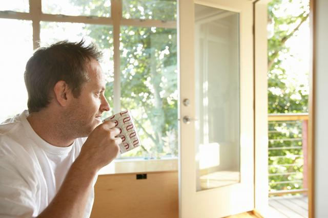 Man sitting by an open window at home